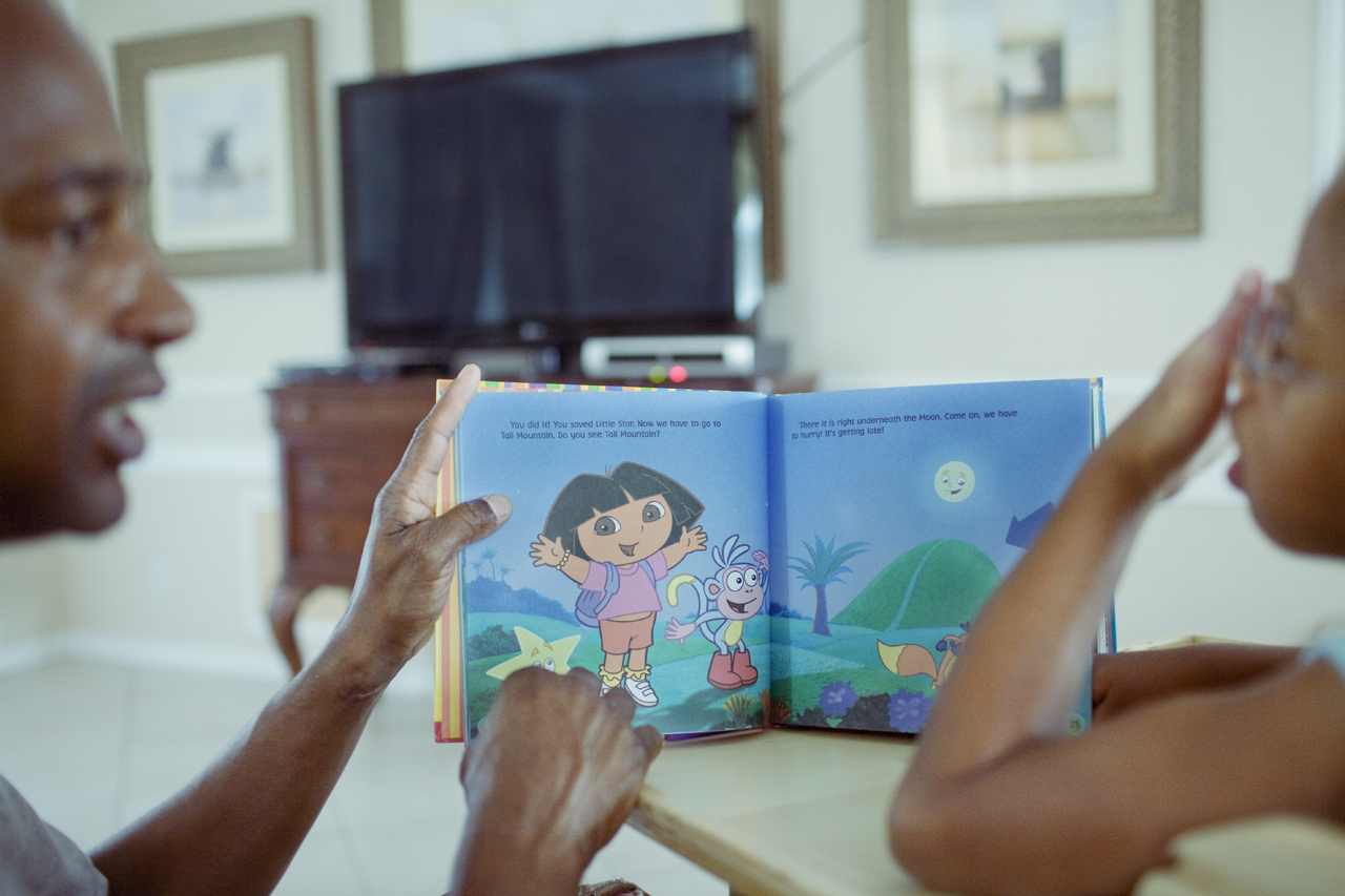 Greenacres, Florida. United States, May, 2009. Ollie Jones teaches his daughter, Janae, to cound with a book featuring Dora the Explorer.