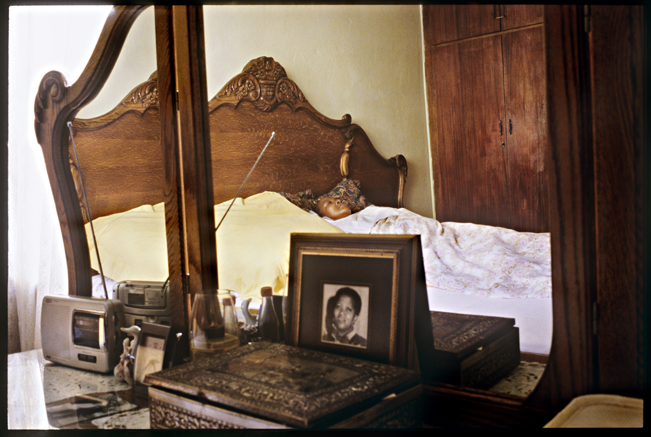 Soweto, Johannesburg, South Africa, August, 2008. Anna Rabotapi in bed and her portrait on top of Maria's chest of drawers in her bedroom. Maria sleeps with Anna every night.